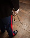 Man i militär likformig med svärdet som lågt visar - halva av kroppen endast Royaltyfri Fotografi