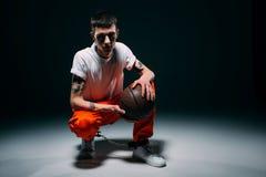 Man i orange flåsanden och manschetter som rymmer basketbollen arkivfoton