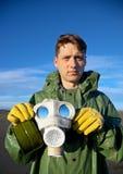 Man i overaller med en gasmask arkivbild