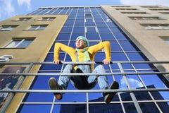 Man i overaller på bakgrund glassed byggnad Arkivfoto