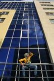 Man i overaller på bakgrund glassed byggnad Fotografering för Bildbyråer