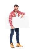 Man, i plakat och att peka för mellanrum för skogsarbetareskjortainnehav Arkivbild