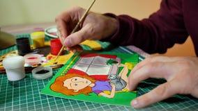 Man i processen av teckningen med bilden för akrylmålarfärger av flickan Fotografering för Bildbyråer