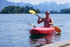 Man i röd kajak på sjön med berg i bakgrund royaltyfria bilder