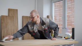 Man i rörande träbräde för exponeringsglas i rum med paneler lager videofilmer
