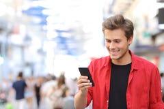 Man i rött smsa på en mobiltelefon Royaltyfri Foto