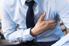 Man i regeringsställning likformign som har den hjärtinfarkt-/hjärtabrännskadan arkivbild