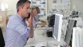 Man i regeringsställning på skrivbordet genom att använda mobiltelefonen och datoren