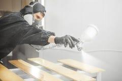 Man i respiratormaskering som målar träplankor på seminariet Arkivbild