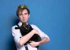 Man i rosa skjorta, suspender och hemlagad guld- krona med den gulliga svarta katten royaltyfria foton