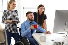 Man i rullstol med hans kollegor fotografering för bildbyråer