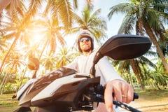 Manisäkerhjälm somrideren mopedunderför vinkellinsför palmträdbrettskott royaltyfri fotografi