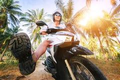 Man i säker hjälm som rider motorcykeln i djungel Exotisk semesterbegreppsbild royaltyfria foton