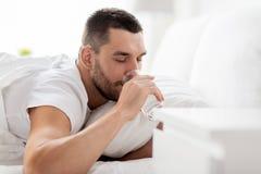 Man i säng med exponeringsglas av vatten som hemma dricker arkivfoton