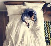 Man i säng som håller ögonen på en TV royaltyfri foto