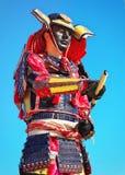 Man i samurajdräkt med svärdet på bakgrund för blå himmel Royaltyfria Bilder
