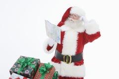 Man i Santa Claus Outfit Reading Road Map royaltyfri foto