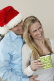 Man i Santa Hat Embracing Woman Holding kaffekopp Arkivbilder