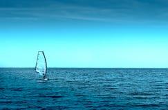 Man i segelbrädor på havet som vindsurfar Arkivfoto