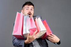 Man i shoppinggalleria stilfull esthete med shoppingpåsen bags tungt Moget shopaholic ferieköp Affär bifokal arkivbild