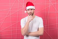 Man i skägg för santa hatthandlag på tänkande framsida Royaltyfria Foton