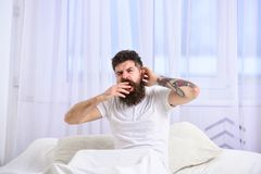 Man i skjorta som gäspar, medan sitt på säng, vit gardin på bakgrund Grabb på sömnigt trött gäspa för framsida Sömntutabegrepp royaltyfri fotografi