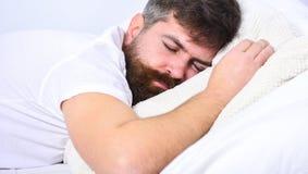 Man i skjorta som lägger på säng, vit vägg på bakgrund Macho med skägget och mustaschen som sover och att koppla av och att ha ta arkivfoton