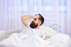 Man i skjorta som lägger på vaken säng, vit gardin på bakgrund Bakrusbegrepp Macho med skägget och mustaschen försova sig Royaltyfri Bild