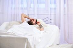 Man i skjorta som lägger på vaken säng, vit gardin på bakgrund Grabb på den besvikna smärtsamma framsidan som vaknar upp i morgon Royaltyfri Bild
