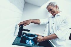 Man i skjortadricksvatten i kök hemma fotografering för bildbyråer