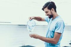 Man i skjortadricksvatten i kök hemma arkivfoto