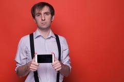 Man i skjortan och suspenderen som rymmer och visar smartphonen royaltyfri bild