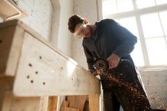 Man i skyddande exponeringsglas genom att använda vinkelmolar för att klippa metall arkivfoto