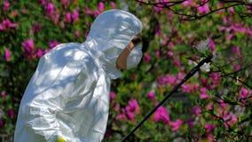 Man i skyddskläder som besprutar kemikalieer stock video