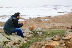 Man i snölandskap genom att använda GPS via hans smartphone arkivbild