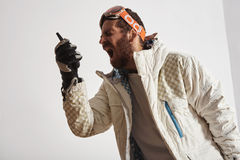 Man i snowboardkugghjul som skriker in i walkietalkie arkivfoto