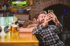 Man i st?ng som dricker ?l Tagandeselfiefoto som minns stor afton i bar F?r hipsterh?ll f?r man sk?ggig smartphone royaltyfria bilder