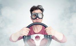 Man i stilfull skyddsglasögon med styrninghjulet på bakgrund, begrepp för bilchaufför royaltyfria foton