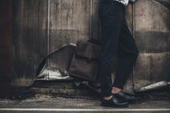 Man i stilfulla flåsanden och skor som står med den bruna påsen nära grungeväggen Arkivbilder
