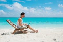 Man i stol med bärbara datorn på stranden arkivfoto