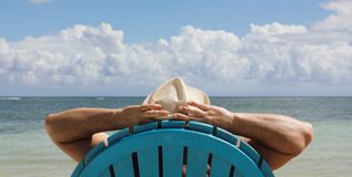 Man i stol på den Caribbian stranden Arkivfoto