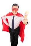 Man i superherodräkten som rymmer en glass Arkivbilder