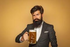 Man i svart dräkt som dricker öl Man med ?l Man med sk?ggdrink?l Retro man med ett ?l Tyck om i bar royaltyfri bild