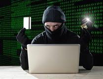 Man i svart hållande kreditkort och lås genom att använda datorbärbara datorn för lösenord för brottslig verksamhetdataintrångban royaltyfri fotografi