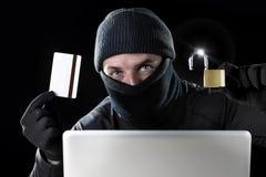 Man i svart hållande kreditkort och lås genom att använda datorbärbara datorn för lösenord för brottslig verksamhetdataintrångban Royaltyfria Bilder