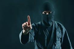 Man i svart maskering med att peka upp fingret royaltyfria foton