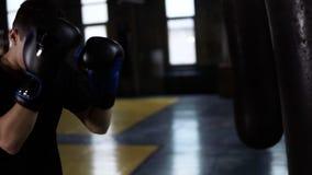 Man i svart T-tröja, determinated boxare som inomhus gör slag på en boxas påse i idrottshallen Kämpe som bara in utbildar lager videofilmer