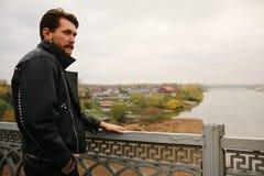 Man i svarta läderomslag som ser floden Royaltyfri Fotografi