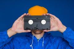 Man i 90-talsportomslag och gul hatt med VHS kassetten på blå bakgrund fotografering för bildbyråer
