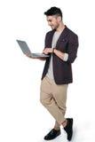 Man i tillfällig kläder som skriver bärbara datorn som isoleras på vit arkivfoto